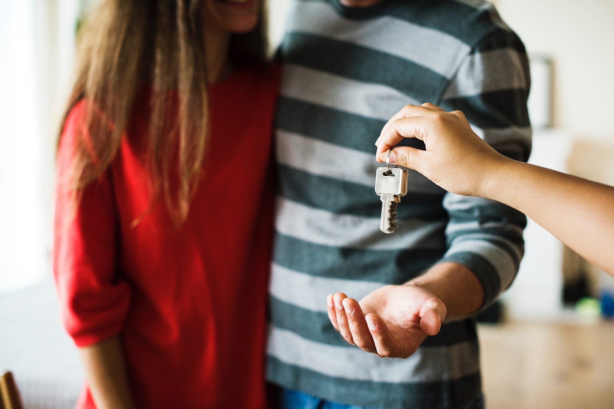 Picture of a couple being handed their keys by a real estate agent